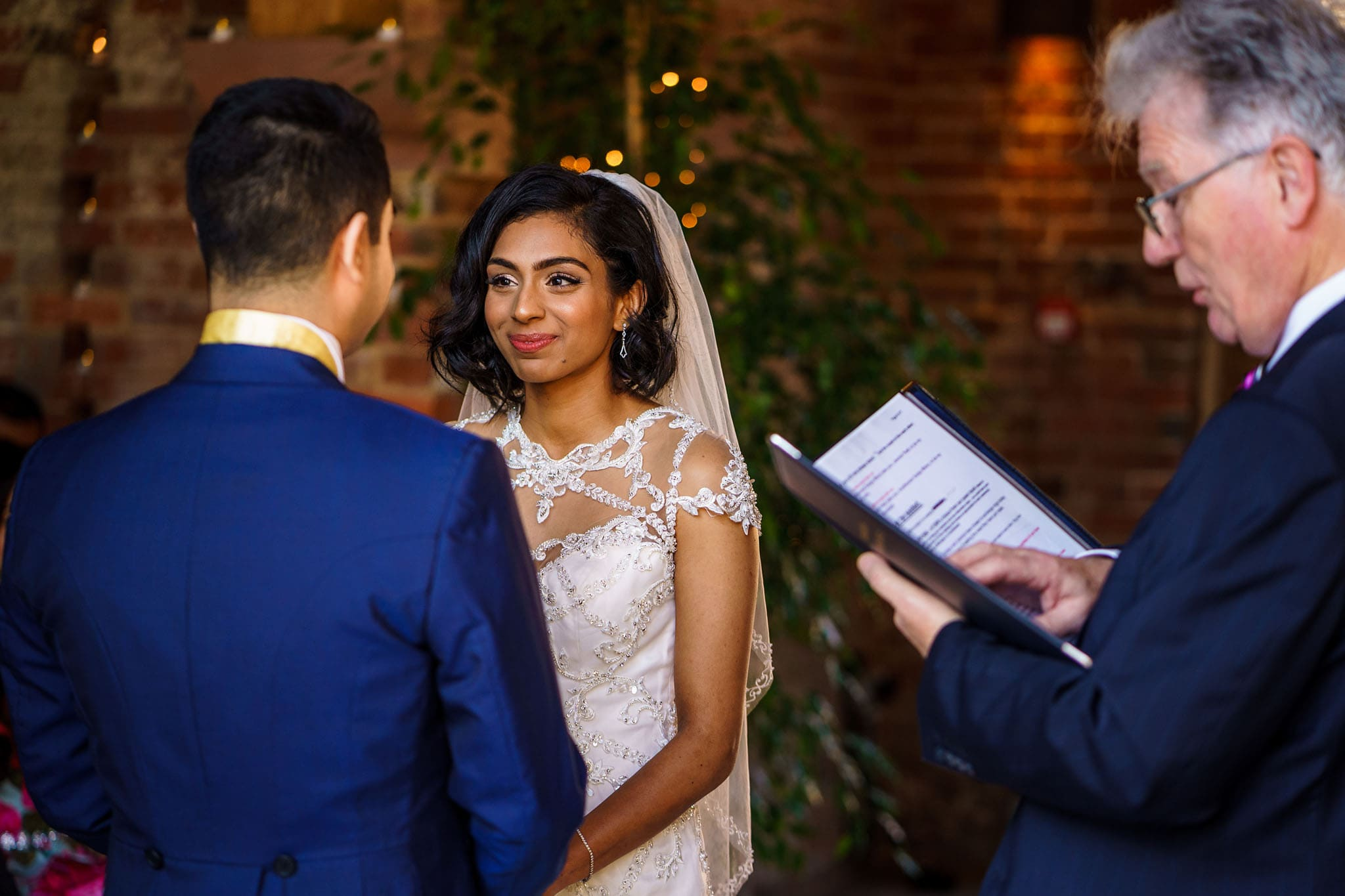 a very happy looking bride smiling at the groom during the ceremony