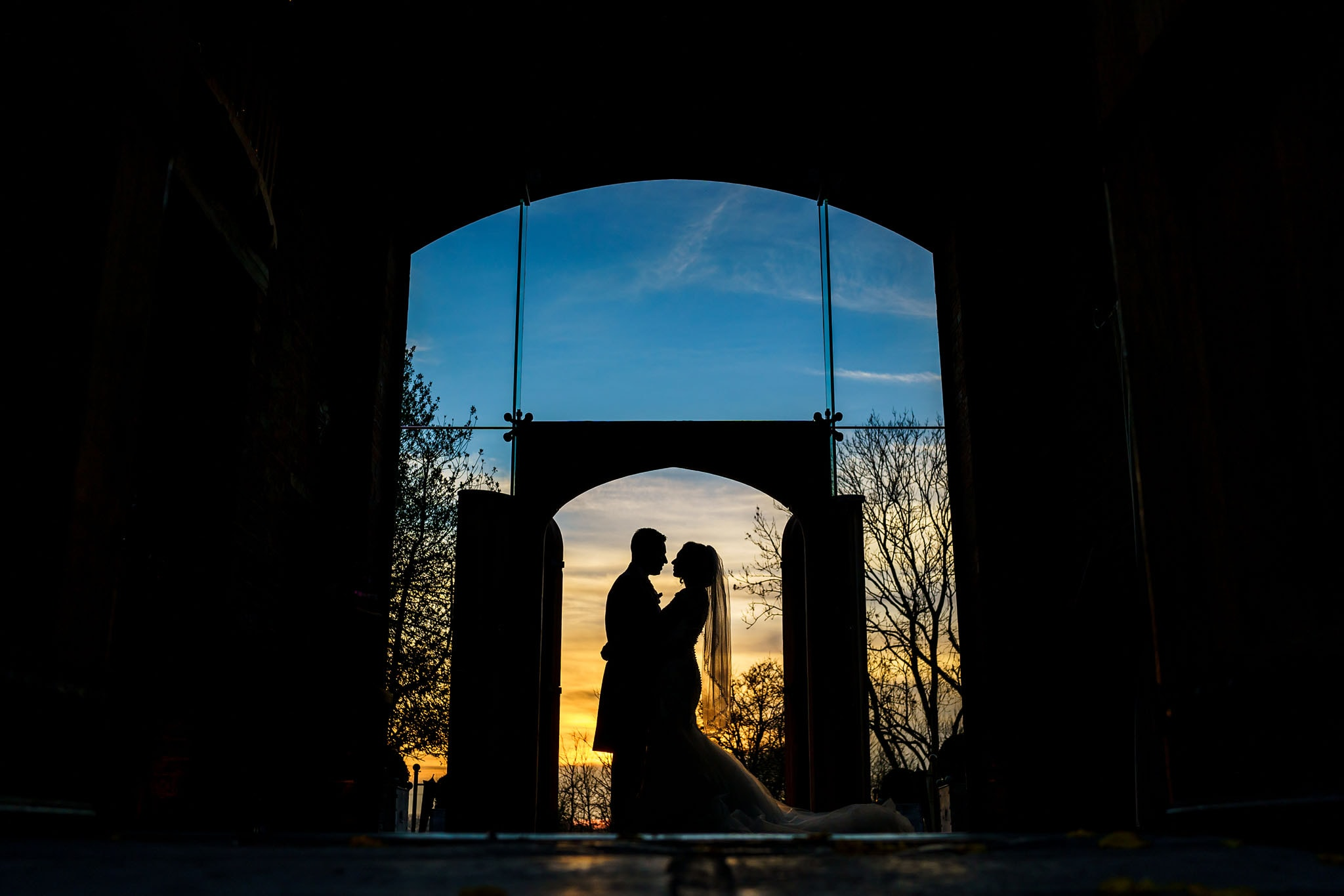 silhouette of the bride and groom during sunset at Shustoke Barn