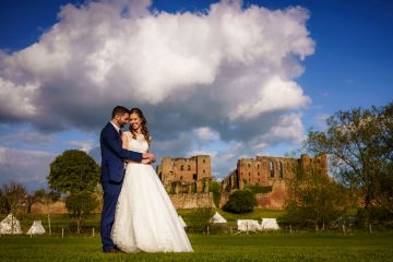 portrait of the bride and groom in front of Kenilworth Castle