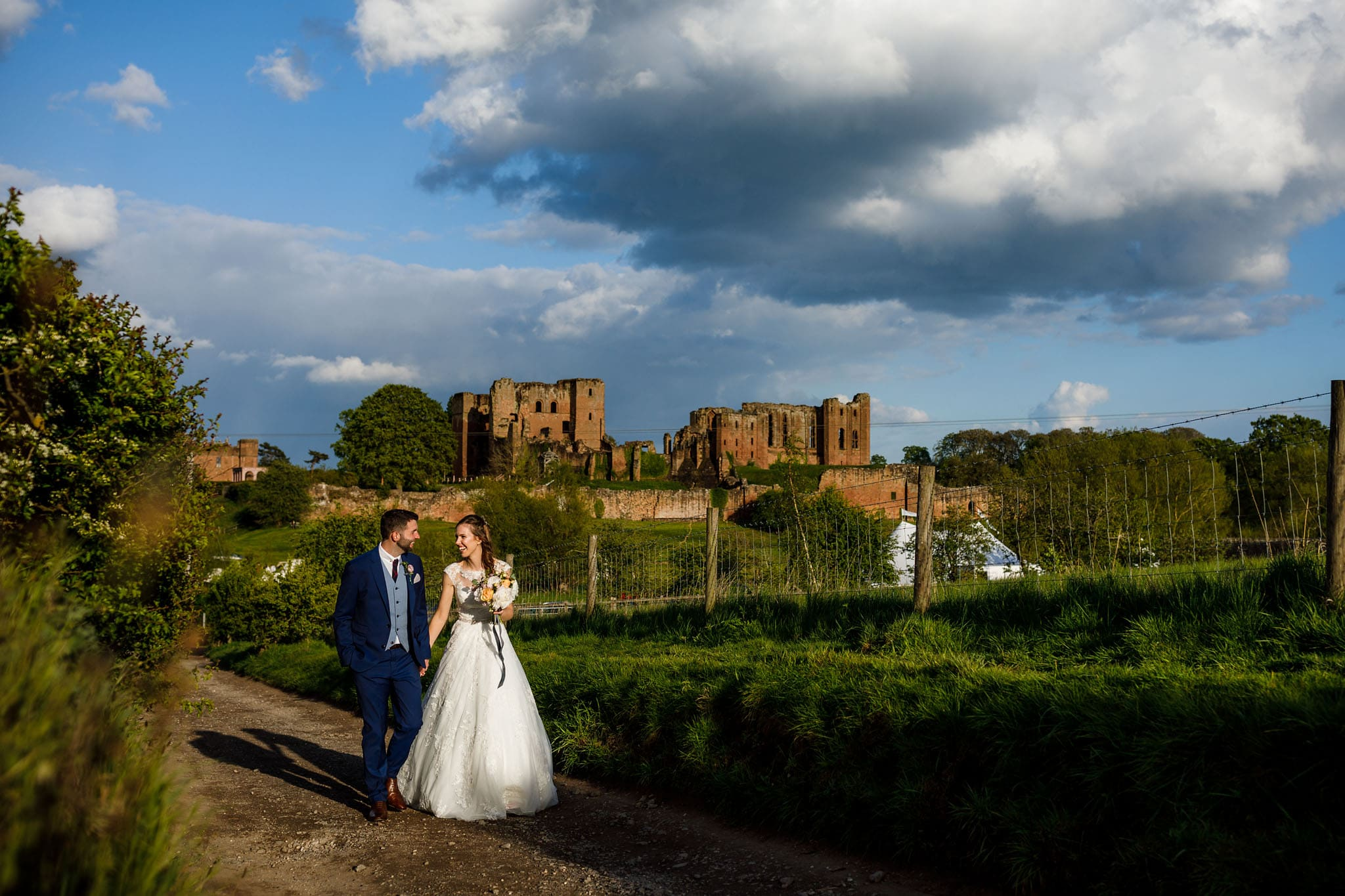 walking couple shot with Kenilworth Castle in the background