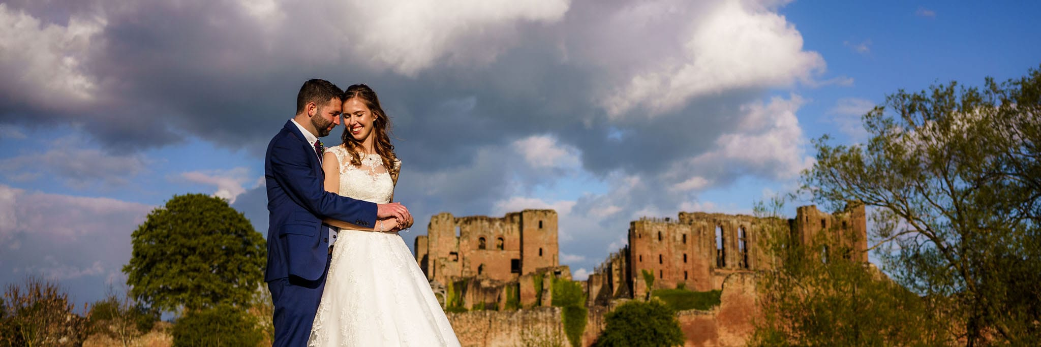 sunlit portrait of the happy couple in front of Kenilwroth Castle