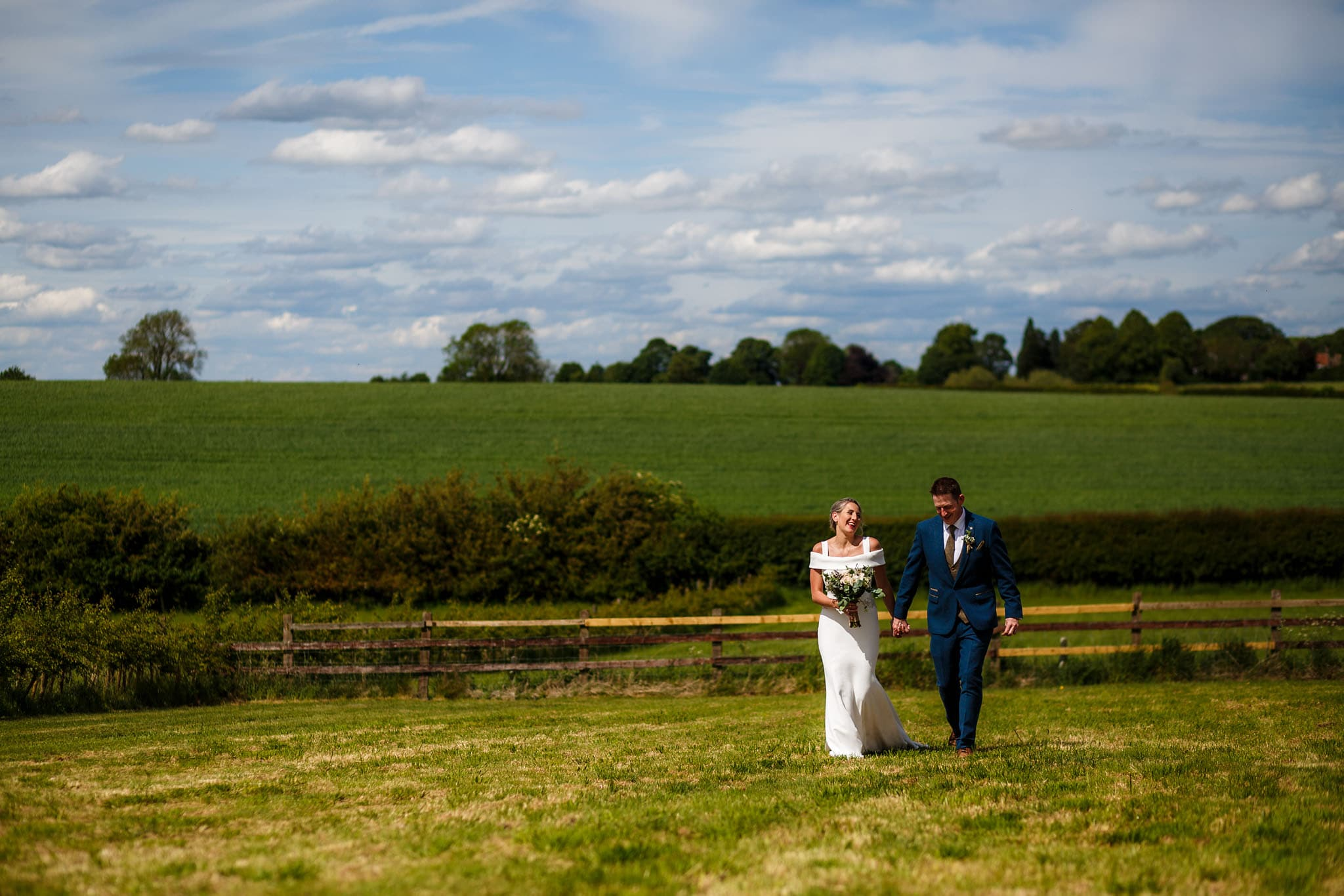 bride and groom walking through the fields togther