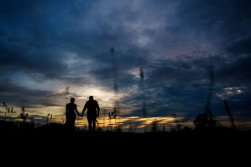 sunset silhouette of the bride and groom walking in the countryside