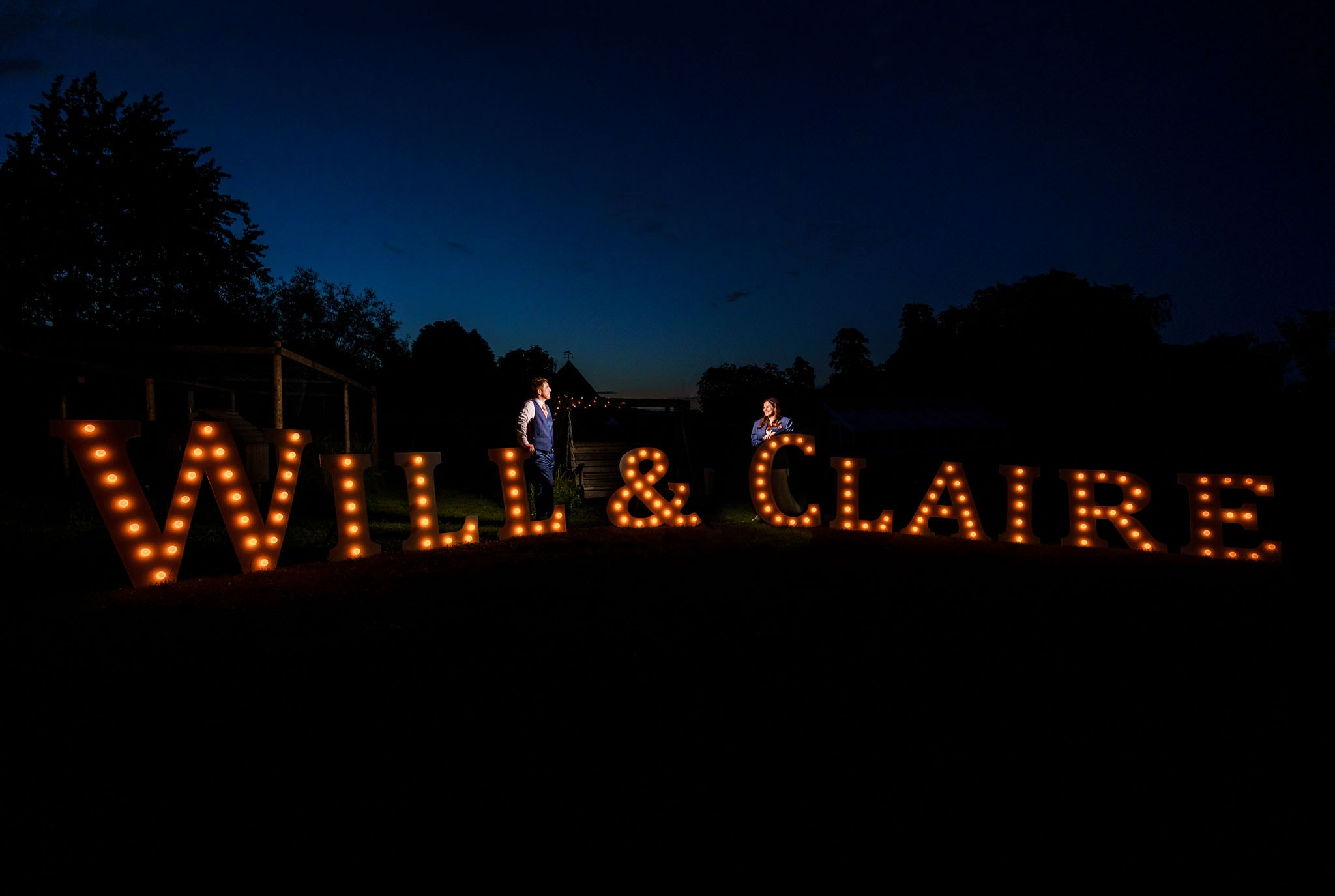 night time portrait of the bride and groom with their light up letters