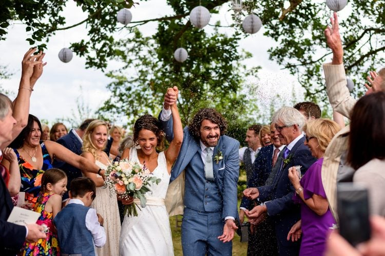 bride and groom getting covered in confetti during their rustic wedding