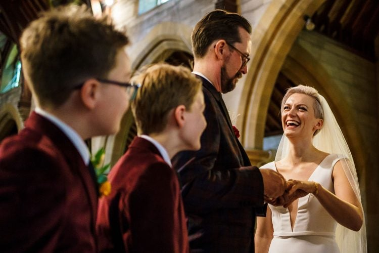 children looking on as the groom has trouble putting the ring on his bride's finger