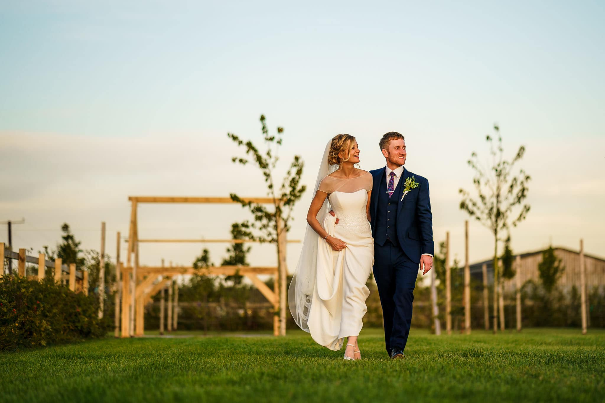 bride and groom walking together in the evening sunshine